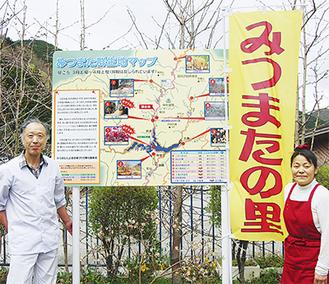 看板の横に立つ高橋会長(左)と湯川さん(右)