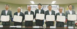 署名した規約書を手にする2市5町の首長たち