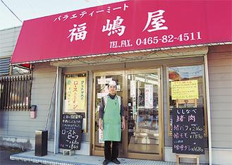 店舗前に立つ小林義幸さん