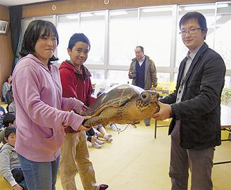 小学生から山本学芸員にアカウミガメが手渡された
