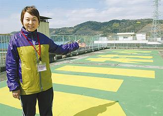 緑地に黄色の文字で「川村小」と表示されている。制作過程を説明する高橋会長