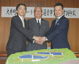 握手を交わす間宮町長(中)、古川社長(右)、黒川副知事(左)