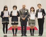 ◀代表して表彰を受けた入選者と佐藤会長(中央)