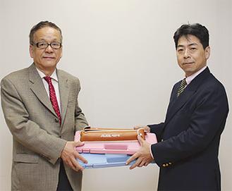 楽器を手渡す松島前会長(右)