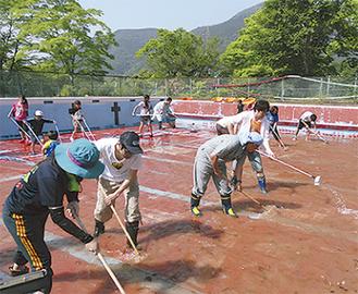 プールを掃除する参加者たち