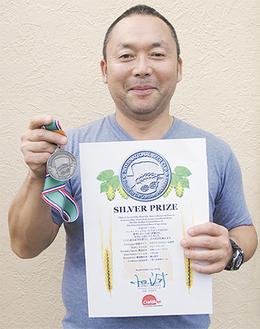 銀メダルと賞状を手にする横山社長
