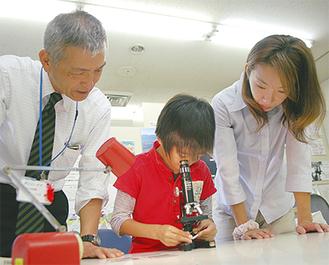 顕微鏡を覗く想くんと恵美子さん、左は一寸木園長=20日・大井町生涯学習センター展示室