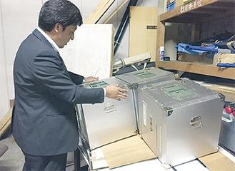 役場の倉庫で期日前投票の投票箱を確認する選管の職員 =25日