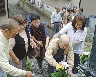 甲一さんの墓参りを家族が見守った=6月12日・山北町の関さん宅