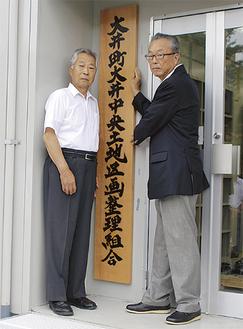 看板をかける間宮町長(右)と露木理事長(左)