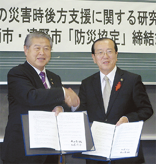握手をかわす加藤市長(左)と本田市長(右)=22日・岩手県遠野市