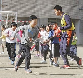 サッカー部員と鬼ごっこをする小学生たち=立花学園グラウンド・11日