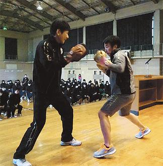 壇上でミット打ちを披露する松田さん(右)=足柄台中学校体育館