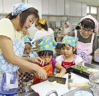 指導を受けて野菜を切る子どもたち