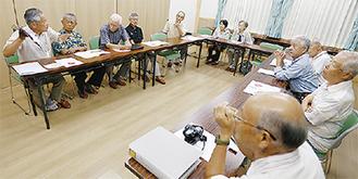 写真とあわせて体験談を話す会員(左)=26日、飯沢公民館
