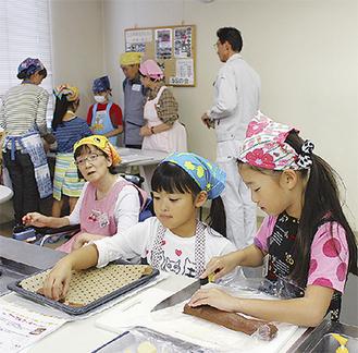 クッキーを作る小学生と見守る加藤さん(手前左)
