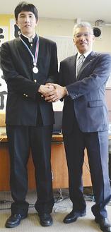府川町長(右)と握手する加藤君(左)身長は191cm