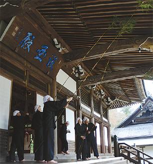 本堂で竹を振る僧侶