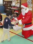 子どもたちの目線に合わせてかがみ、一人ひとりにプレゼントを手渡した=12月15日撮影