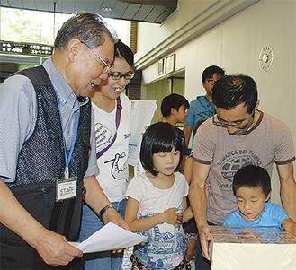 「1億円」の重さを体験する親子 =大井町生涯学習センター