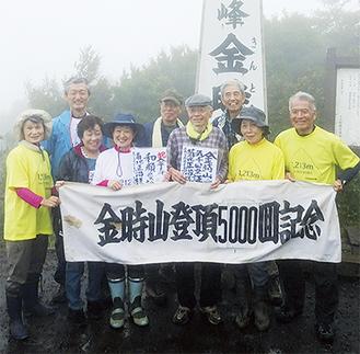 仲間に祝福される菊地さん(中央)=金時山山頂・4日朝