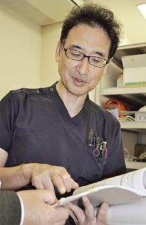 資料を手に打ち合わせをする清水智明医師