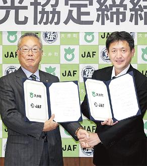 協定書を交わす間宮町長(左)とJAF神奈川支部の川喜田大明事務所長         =13日・大井町役場