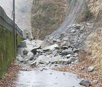 落石が林道を覆う崩落現場(17日朝・県提供)