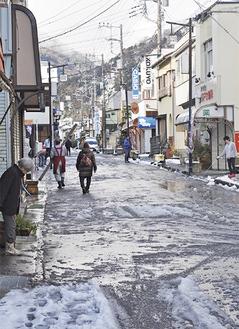 通りに出て雪かきをする住民=山北駅前・1月23日午前9時