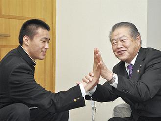 加藤市長と手のひらを合わせる榎本選手 =南足柄市役所