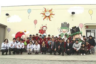 イラストが描かれたわかば園舎の外壁(前列中央左側が阿部社長、左隣りが岡本さん)