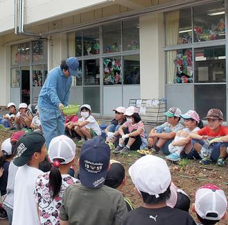 野菜部員(中央)が児童に野菜作りを教えた