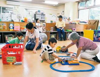こどもと遊ぶシルバー会員の清水さん(中央奥)と高橋さん(右手前)、保育士の吉田さん(中央左) =おかもと福祉館