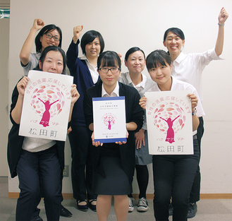総合戦略の冊子とロゴマークを手にする松田町の女性職員