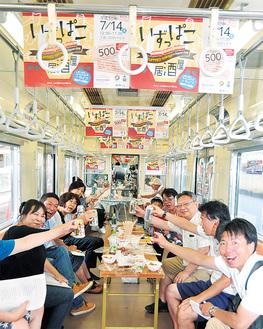 電車の中で居酒屋の雰囲気を楽しむ参加者たち