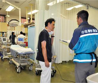 救急隊員から患者の様子を聞く清水智明救命救急部長=足柄上病院
