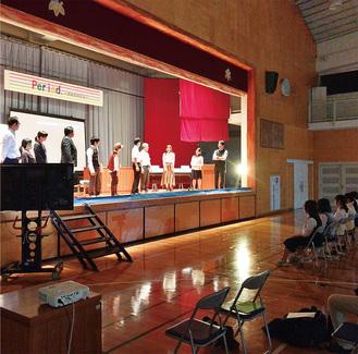 最前列に座る生徒の前で演劇を披露する職員