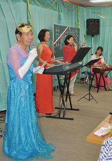 演奏に合わせドレス姿で踊りを披露した杉山さん(手前)=榎本公会堂