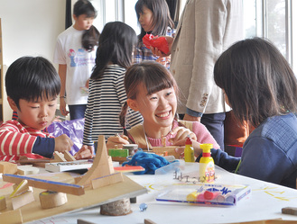 校舎2階のちびっこ工作で子どもたちと作品作りを楽しむボランティアの学生スタッフ(中央)