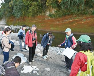 千貫岩と川辺にある石の特長を解説するガイド