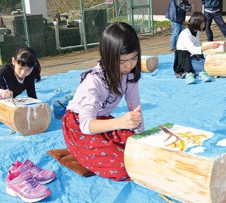 自由な発想で丸太に描く小学生たち