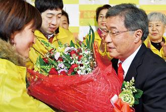 支持者から当選祝いの花束を受け取る小田氏(右)=12月9日・大井町金手の選挙事務所で