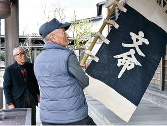 文命幟を手にする山口さんと研究家の大脇良夫さん=南足柄市怒田・福澤神社