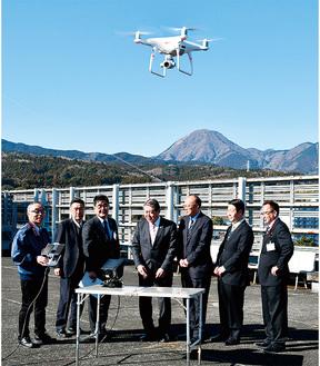 市役所屋上での試験飛行を視察する市長と議会関係者
