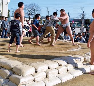 頑丈に生まれ変わった土俵で相撲をとる児童たち