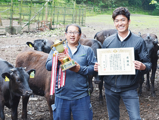 牧場で飼育している牛と長崎牧場の長崎さん(左)と中川食肉の中川さん