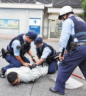 犯人役の男は駆けつけた警察官に取り押さえられた