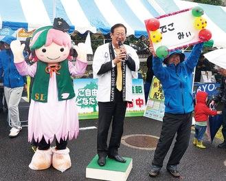 当日の投票により決まった「でごにぃ」の妹キャラ(左)の命名発表シーン。中央は湯川町長