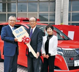 車両の前で府川町長(左)にレプリカキーを渡す辻村夫妻