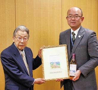 横山さん(左)と本山町長。右下は寄贈された絵
